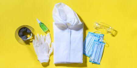 Folding medical protective clothing, masks, glasses and sanitizer on yellow