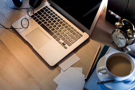 Heimarbeitsplatz mit Computerlaptop, Kaffee, Lampe auf dem Tisch. Aus der Ferne zu Hause. Bleiben Sie während der Quarantäne zu Hause und arbeiten Sie online. Online-Bildung. Krise. Leer Standard-Bild