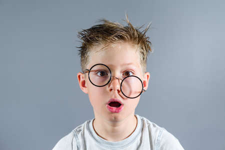 Shocked schoolboy with eyeglasses on the face and messy hair after online lessons at home.