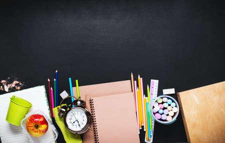 概念回到学校闹钟颜色白垩铅笔在黑板背景的苹果笔记本文具。设计副本空间用品顶视图平躺