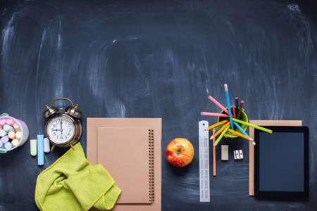 Back to school concept. Office supplies. Stationery on blue blackboard background alarm clock, color chalks, pencil, apple, notebook. Copy space. Top view. Flat lay.
