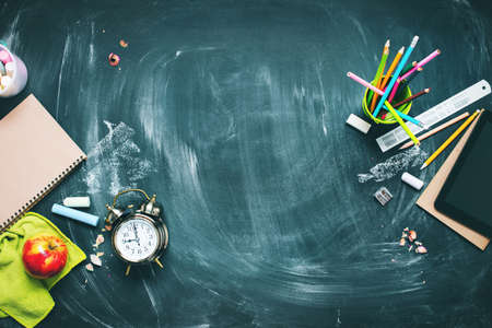 Back to school concept. Office supplies. Stationery on green blackboard background alarm clock, color chalks, pencil, apple, notebook. Copy space. Top view. Flat lay.