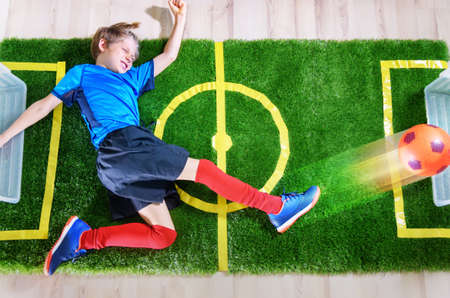Boy imitating soccer game with kicking the ball on green field near TV screen at home during the quarantine. Stay at home. Sport activities. Coronavirus situation. Top view
