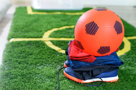 Orange soccer ball on top of uniform and shoes on green field for kids at home. Quarantine. Stay at home. Sport activities. Coronavirus situation. Football game indoor. Colorful. Lockdown.
