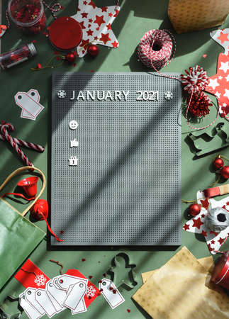 A woman creates a plan for a year on a typesetting plastic board in white letters. Calendar flat lay. Christmas time 2021 plan