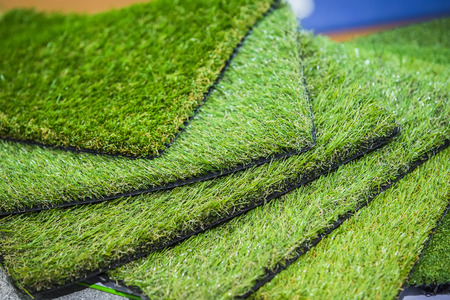 Green artificial turf rolled. Probes examples of artificial turf, floor coverings for playgrounds. Stockfoto