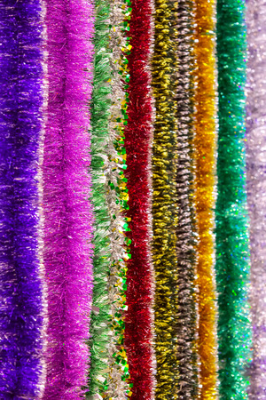 The colorful multi color of tinsel for a background. Vertical texture of multi-colored New Years tinsel.