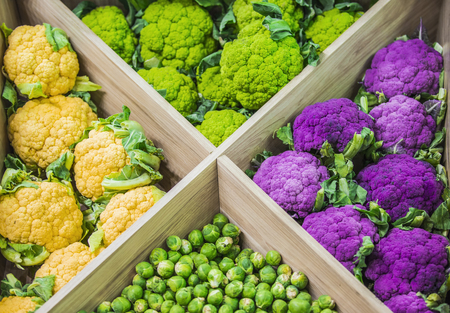 Fresh colorful vegetables on the counter of the store: colorful cauliflower, Brussels sprouts.