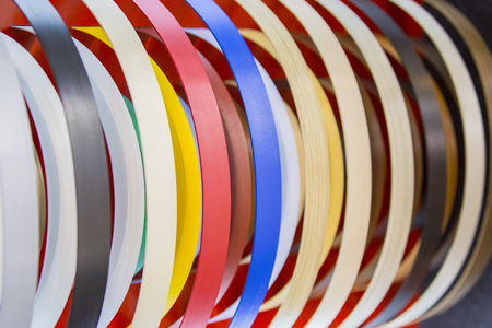 Solid color or wood grain PVC edge banding tape. ABS edge banding. Set of colored thermoplastic edges. Multicolored bobbins of PVC edge and melanin for the manufacture of furniture.
