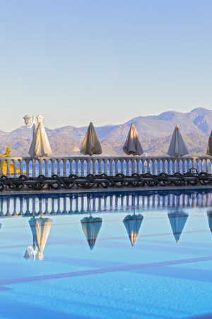 Row of empty sunbeds by the pool and the sea in the morning at dawn. Comfortable high-rise hotel. Stock Photo