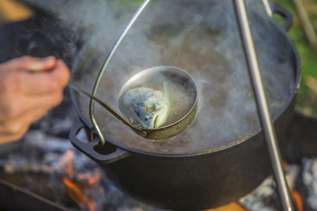 Fish soup boils in cauldron at the stake. Soup in a pot in the fire.