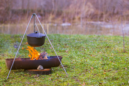 A field pot with soup in the fire. Traveling on nature tourism. Stock Photo