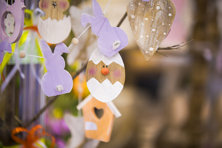 Colorful handmade wooden Easter elements: eggs, rabbits, chick. Easter bright, abstract, blurred background. Easter tree.