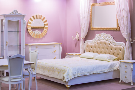 Luxury white bedroom in antique style with rich decor . Interior of a classic style bedroom in luxury apartment.