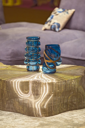 Blue fashionable glass vases on the gold cooper modern table. Stylish interior art deco.
