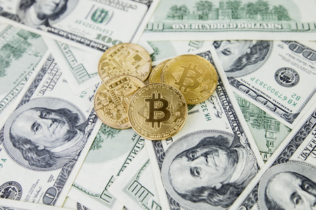 The gold coin bitcoin lies on a stack of hundred dollar bills. Crypto currency, physical coin. Exchange bitcoin for a dollar. Conceptual image for worldwide cryptocurrency and digital payment system.