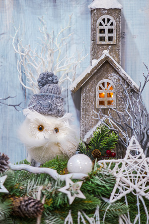 Beautiful magic house in Christmas decorations with a toy owl in hat.