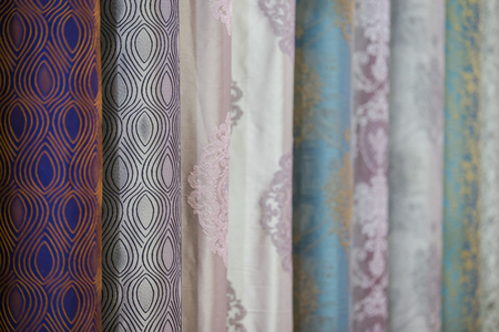 Curtain samples hanging from hangers on rail in store. Fabric texture samples selection fabrics for interior decoration Curtains, tulle and furniture upholstery. 写真素材