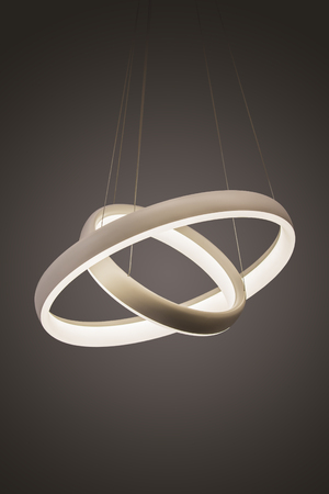 Modern led pendant light lamp illuminated, fashionable designer chandelier in the form of rings. 免版税图像