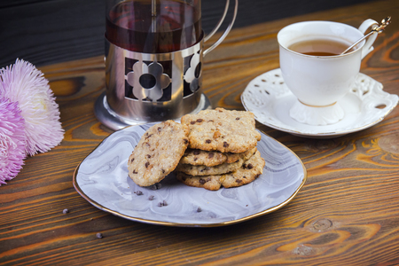 Homemade chocolate chip cookies on a beautiful saucer, kettle of tea, on a wooden dark background.