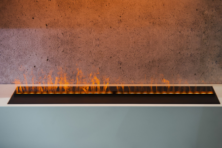Minimalism interior, modern alternative fireplace with imitation of flame. Designer electric fireplace.