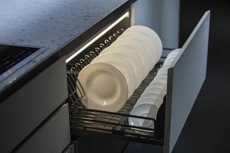 Modern kitchen, storage space for plates, illuminated drawer in luxury kitchen.