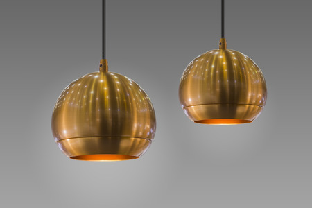 Modern streamlined mirror round copper chandelier. Bubble gold pendant light. Isolate on gray background.