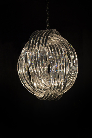 Fashionable designer chandelier in the form of rings decorated with glass crystals diamonds, chandelier isolate on a black background.