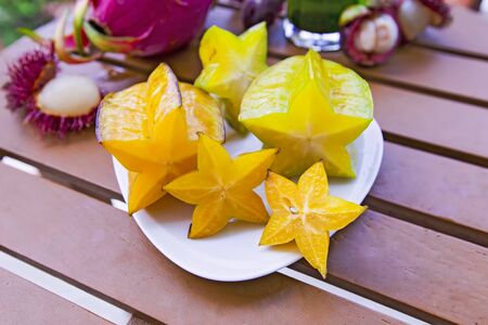 Mix of fresh fruits from Thailand, dragon fruit, rambutan, carambola, mangosteen up view. Sliced beautiful fresh tropical fruits. Stock Photo