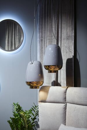 Vase-shaped pendant lights, ceramic lampshade, blue colored chandelier with a gold bottom. Luxury modern interior.