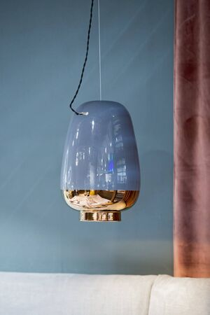 Pendant lamp in the shape of a vase, ceramic lampshade, blue colored chandelier with gold trim. Design luxury interior.