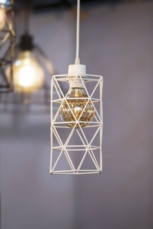 Pendant lamp geometric shape lampshade, white metal chandelier with a gold lamp inside. Design loft.