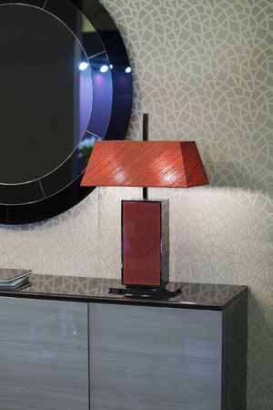 Red fashionable bedside lamp, modern lamp in the interior.
