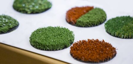 Green and red artificial turf rolled. Probes examples of artificial turf, floor coverings for playgrounds. Banque d'images - 129018886
