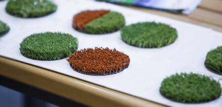 Green and red artificial turf rolled. Probes examples of artificial turf, floor coverings for playgrounds. Selective focus. Banque d'images - 129018889