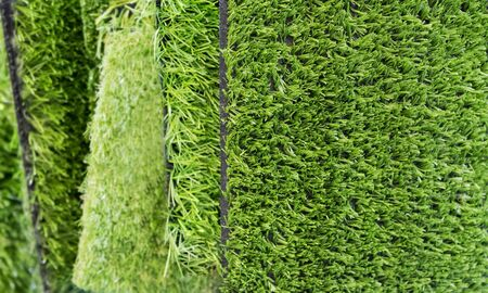 Green artificial turf rolled. Probes examples of artificial turf, floor coverings for playgrounds. Selective focus. Banque d'images - 129018893