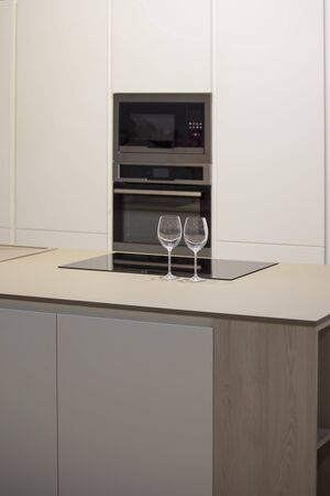 Minimalistic kitchen design with island. Gray-white kitchen and wine glasses on the table.