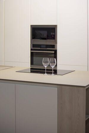 Minimalistische keukeninrichting met eiland. Grijs-witte keuken en wijnglazen op tafel.
