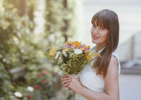 Beautiful girl in a summer dress with a bouquet in her hands in the park. Portrait of a beautiful brown-haired woman in the summer with flowers. Bride.