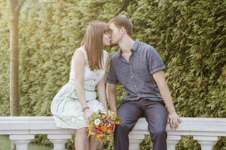 Ein Liebespaar, eine Liebesgeschichte, ein Mann und ein Mädchen, ein Brautpaar mit einem Blumenstrauß in der Hand, sich küssend. Glückliches Paar an einem Sommertag im Park.