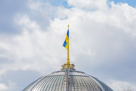 Ukrainian flag on the dome of the building. Yellow-blue flag on a background of the sky with clouds.