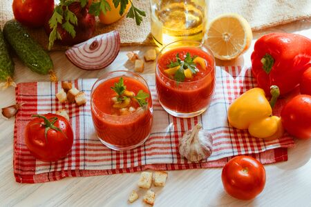 Tomato soup gazpacho in glass with herbs and ingredients on the kitchen. A beautiful summer soup spilled in glasses surrounded by juicy vegetables