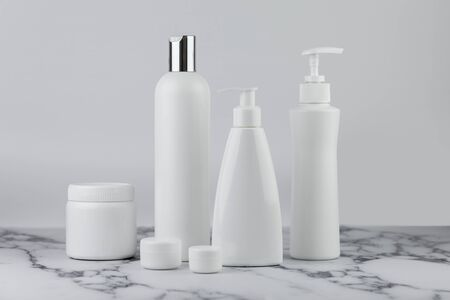 Conjunto de botellas de cosméticos, colección de botellas blancas vacías de crema con dispensador, champú o loción sobre fondo blanco.