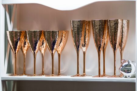 A set of glasses for wine and champagne, gold glasses made of copper with an interesting texture, bronze wine glasses of modern design. Cupboard with glasses.