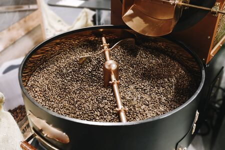 The freshly roasted coffee beans from a large old coffee roaster being stirred in the cooling cylinder. Fresh coffee beans.