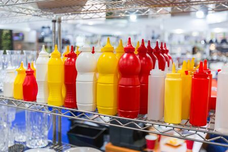 Empty plastic containers, bottles for mayonnaise mustard sauce and ketchup. Gravy boats for a restaurant or cafe folded on a shelf.