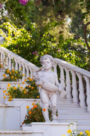 White stone sculpture of a boy with a fish in his hands in the resort town on the stairs.