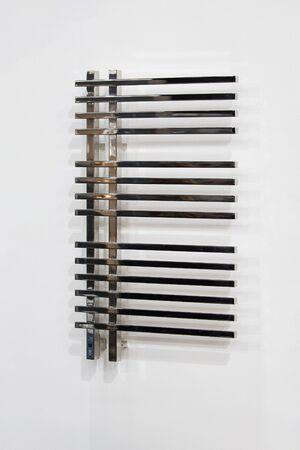 Towel rail chrome bathroom radiator on white background.