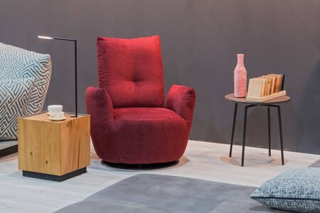 Red armchair wooden table with lamp, small coffee table in the interior. Imagens