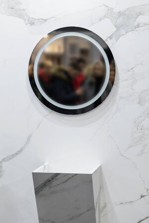 Marble sink on the background of a marble wall, white bathroom completely in marble with round mirror.
